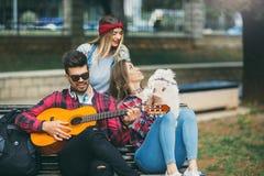 Amigos en el parque que se divierte que toca la guitarra Fotos de archivo libres de regalías