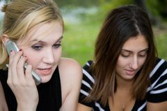Amigos en el teléfono celular junto (Blonde joven hermoso y Brune fotografía de archivo libre de regalías