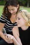 Amigos en el teléfono celular junto (Blonde joven hermoso y Brune Imagenes de archivo