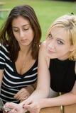 Amigos en el teléfono celular junto (Blonde joven hermoso y Brune Imagen de archivo libre de regalías