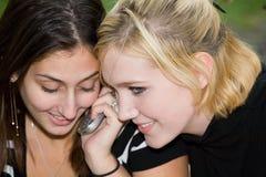 Amigos en el teléfono celular junto (Blonde joven hermoso y Brune Imagen de archivo