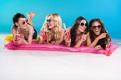 Amigos en gafas de sol que beben los cócteles mientras que miente en los colchones que nadan Imagen de archivo libre de regalías