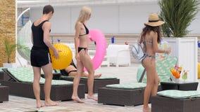 Amigos en la compañía de las vacaciones de verano de la juventud en bañadores con el anillo inflable en el centro turístico costo almacen de video