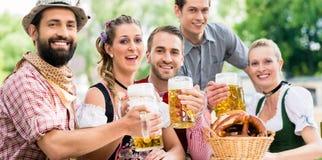 Amigos en la consumición bávara del jardín de la cerveza Fotografía de archivo libre de regalías