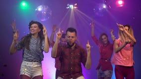 Amigos en la danza de un club nocturno con confeti que cae Fume el fondo colorido C?mara lenta almacen de video