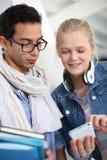 Amigos en la escuela que escuchan la música Foto de archivo libre de regalías