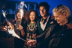 Amigos en la noche con los fuegos artificiales que disfrutan del partido imagen de archivo