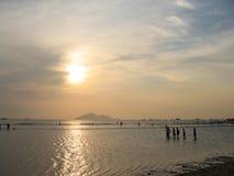Amigos en la playa de la puesta del sol imagen de archivo