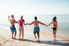 Amigos en la playa Diviértase en el día de verano soleado Imagenes de archivo