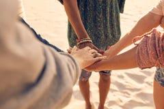 Amigos en la playa que pone las manos juntas Imagen de archivo