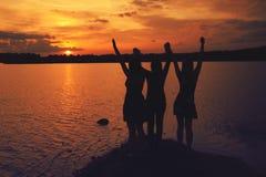 Amigos en la puesta del sol Imagenes de archivo