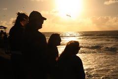 Amigos en la puesta del sol en el océano Foto de archivo