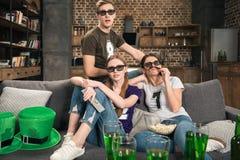 Amigos en los vidrios 3D que miran película Imagenes de archivo
