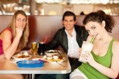 Amigos en restaurante que comen los alimentos de preparación rápida Imágenes de archivo libres de regalías