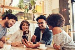 Amigos en un café que mira las fotos en el teléfono móvil foto de archivo