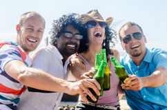 Amigos en un partido de la playa que tiene bebidas imágenes de archivo libres de regalías