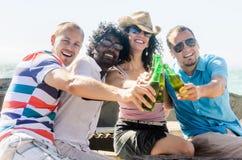 Amigos en un partido de la playa que tiene bebidas fotografía de archivo