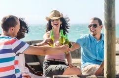 Amigos en un partido de la playa que tiene bebidas fotos de archivo
