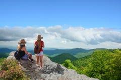 Amigos en un viaje que camina en las montañas Imagen de archivo libre de regalías