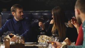 Amigos en un vino de consumición del restaurante almacen de video