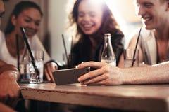 Amigos en una barra que miran el vídeo divertido en el teléfono móvil Fotos de archivo