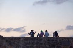 Amigos en una pared colonial imagen de archivo