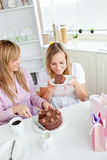 Amigos encantados de las mujeres que comen una torta de chocolate Foto de archivo libre de regalías