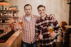 Amigos encontrados después de un día duro La cerveza alegre del tintineo del amigo tres en la barra y bebe una cerveza en la barr imagenes de archivo