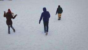 Amigos engraçados que jogam na neve em um dia de inverno brilhante Movimento lento Tiro aéreo filme