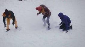 Amigos engraçados que jogam na neve em um dia de inverno brilhante Movimento lento Tiro aéreo vídeos de arquivo