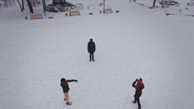 Amigos engraçados que jogam na neve em um dia de inverno brilhante Tiro aéreo do zangão filme
