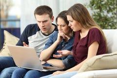 Amigos enojados que miran el contenido en un ordenador portátil Fotos de archivo libres de regalías