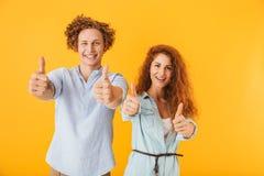 Amigos entusiasmado que amam os pares que mostram os polegares acima imagem de stock