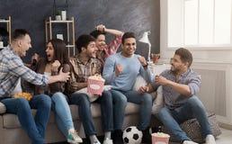 Amigos entusiasmado que olham o fósforo de futebol em casa imagem de stock
