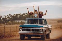 Amigos entusiasmado que viajam por um camionete fotos de stock royalty free