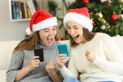 Amigos entusiasmados que olham o índice do telefone no Natal fotografia de stock