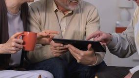 Amigos envejecidos que miran las fotos a partir de vacaciones en la tableta y que ríen, divirtiéndose metrajes