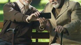 Amigos envelhecidos felizes que tomam o selfie pelo smartphone fora, olhando o vídeo em linha vídeos de arquivo