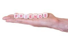 Amigos escritos com dados de madeira em uma mão, isolada no fundo branco Imagens de Stock Royalty Free