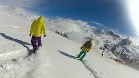 Amigos extremos que montam a inclinação de montanha nevado dos snowboards para baixo, lazer ativo vídeos de arquivo