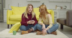 Amigos fêmeas alegres que compartilham do telefone esperto em casa video estoque