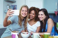 Amigos fêmeas alegres que tomam o selfie foto de stock royalty free
