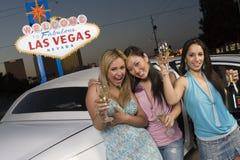 Amigos fêmeas com Champagne Standing By Limousine Fotos de Stock Royalty Free