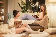 Amigos fêmeas com livro e bloco de desenho em casa Fotos de Stock Royalty Free