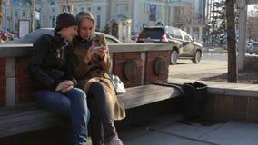 Amigos fêmeas com o smartphone que tem o riso de sorriso do divertimento na rua da cidade filme