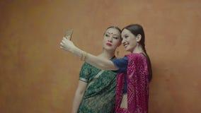 Amigos fêmeas do estilo indiano que levantam para o tiro do selfie vídeos de arquivo