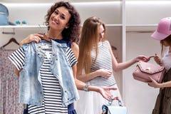 Amigos fêmeas engraçados felizes que escolhem a roupa nova e os acessórios que olham a câmera no boutique fotos de stock royalty free