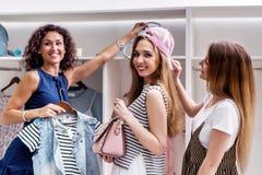 Amigos fêmeas engraçados felizes que escolhem a roupa nova e os acessórios que olham a câmera no boutique foto de stock