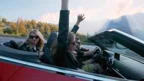 Amigos fêmeas europeus atrativos que cantam, dançando e aplaudindo conduzindo o carro superior aberto luxuoso ao longo das montan video estoque