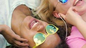 Amigos fêmeas felizes nos fones de ouvido que escutam a música junto, encontrando-se na grama filme